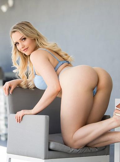 La mejor actriz porno, Mia Malkova en ropa interior celeste de rodillas en un sofá.