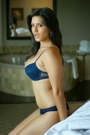 Una Sunny Leone muy excitada posa a un costado de la cama.