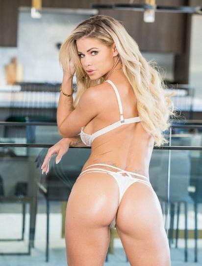 Jessa Rhodes posa de espalda y nos mira mientras lleva una sexy ropa interior blanca.