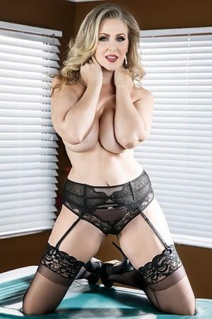 Julia Ann, una de las actrices porno maduras dedicadas al lesbianismo, posa de rodillas cubriendo sus tetas con los brazos.