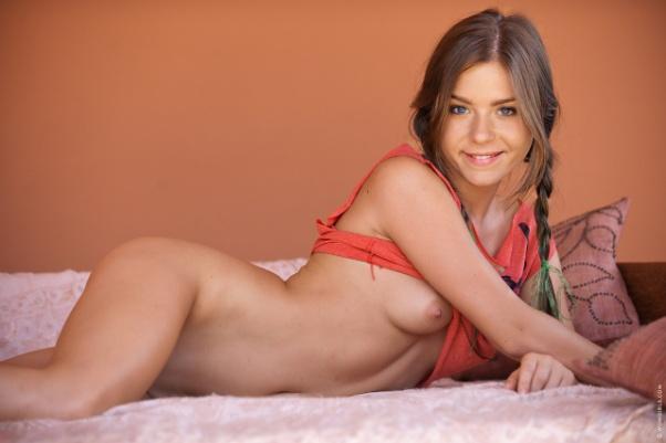 Con la cara más angelical de las actrices porno rusas, Marina María sonríe a la cámara acostada casi desnuda en la cama.