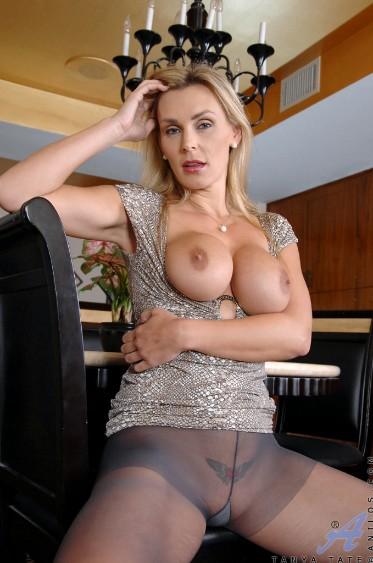 Múltiple ganadora de premios entre las actrices porno maduras, Tanya Tate se sienta, se baja la blusa para enseñar sus teta y mirar con deseo de ser follada.