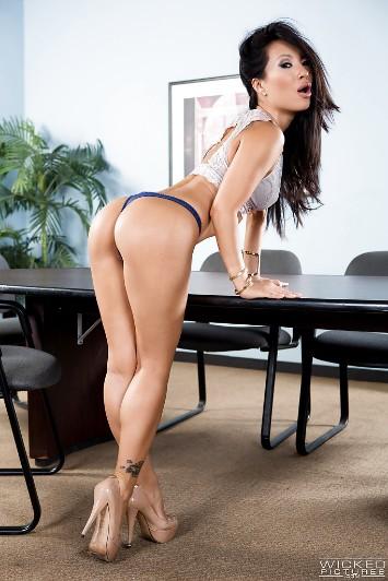 La asiática Asa Akira, de las actrices porno famosas, está de pie en una sala de conferencias, llevando ropa muy excitante.